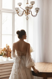 Молодая модель в винтажном свадебном платье с обнаженной спиной позирует в винтажном интерьере ...