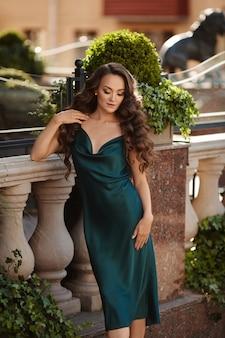 夏の日に街の通りでポーズをとってミディドレスで巻き毛の若いモデルの女性