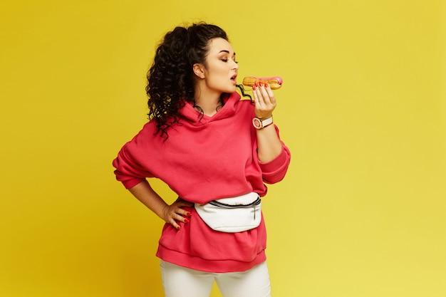 分離された黄色の背景においしいデザートを食べるピンクのパーカーに巻き毛の若いモデル女性