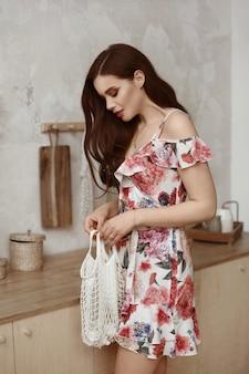 完全な唇とキッチンのインテリアでポーズをとって短い夏のドレスで完璧なメイクの若いモデルの女性