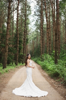 Young model woman with jewelry in her bridal hairstyle wearing in stylish lace wedding dress posing in the forest.