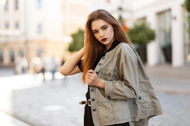 도시에서 포즈 유행 재킷에 메이크업 젊은 모델 여자