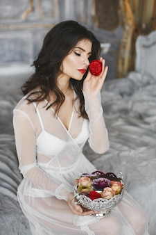 Young model woman with perfect body in white lingerie and in peignoir sits on a bed with vase full of flowers
