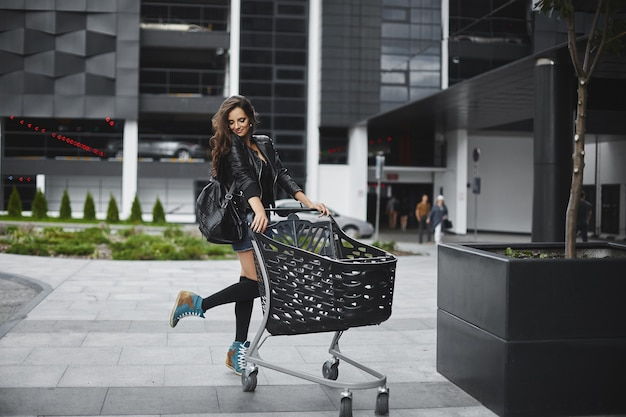 Young model woman with perfect slim body in shorts and leather jacket posing with a shopping cart on the street near the store