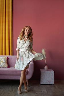 ヴィンテージのインテリアでポーズをとる流行の夏のドレスを着てスリムな完璧なボディを持つ若いモデルの女性