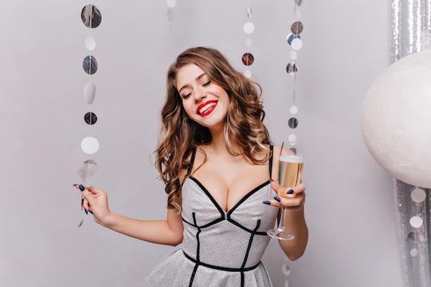 매우 아름다운 머리를 가진 젊은 모델 여자는 그녀의 축제 실버 드레스에 매우 아름답게 미소