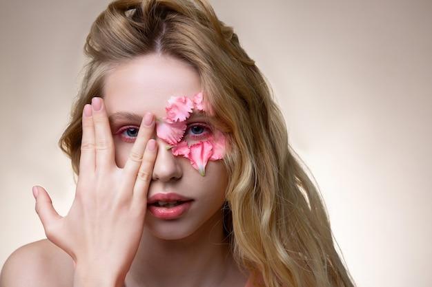 若いモデル。素敵なポーズを示す顔にピンクの小さな花びらを持つ若いプロのモデル