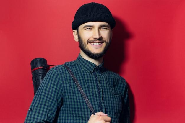 Молодой современный архитектор, улыбающийся человек, несущий трубку для рисования, изолированную на красной стене.