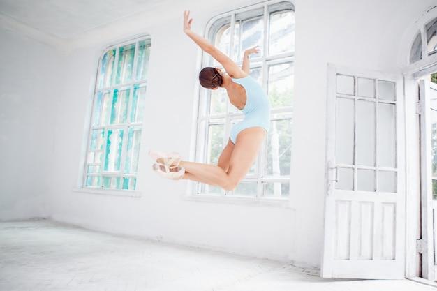 Молодой современный танцор балета прыгает на белом фоне