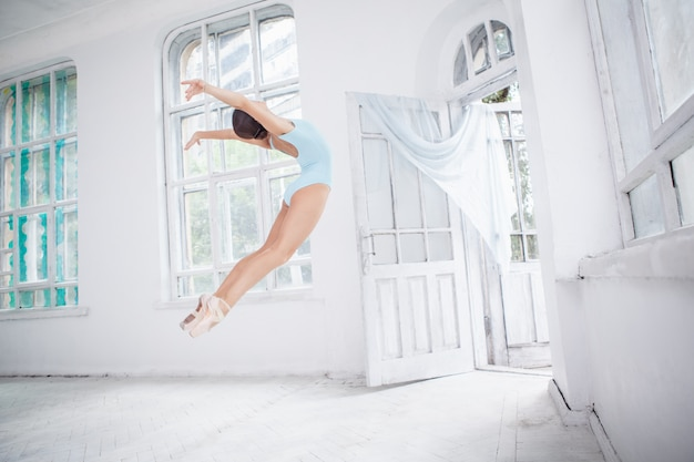 Young modern ballet dancer jumping on white wall