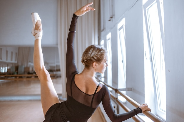 The young modern ballet dancer posing against the room wall