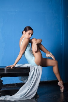 水色の壁でポーズをとって若い現代バレエダンサー