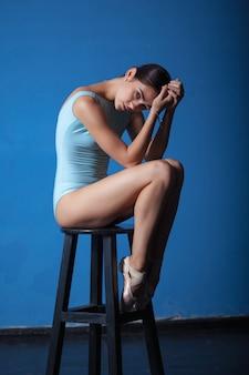 青でポーズをとって若い現代バレエダンサー