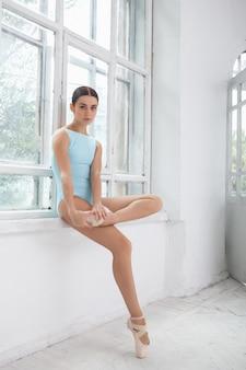 白でポーズをとる若い現代のバレエダンサー