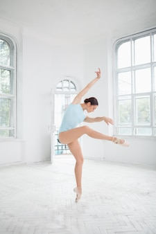 Young modern ballet dancer posing on white wall