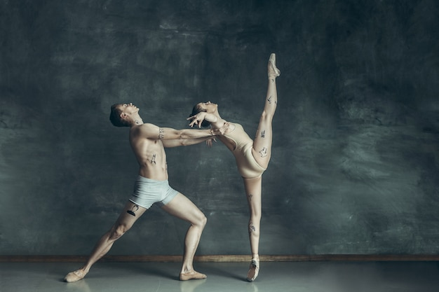 Young modern ballet dancers posing on gray