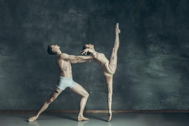 灰色でポーズをとって若い現代バレエダンサー