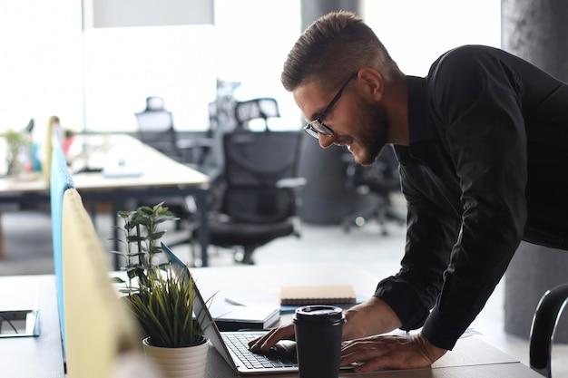 Молодой современный деловой человек анализирует данные с помощью ноутбука во время работы в офисе.