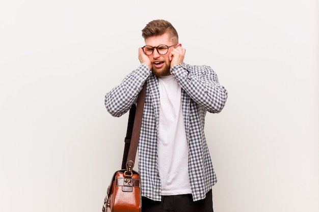 Young modern business man covering ears with his hands.