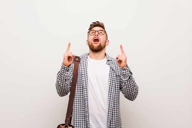 Young modern business man pointing upside with opened mouth.