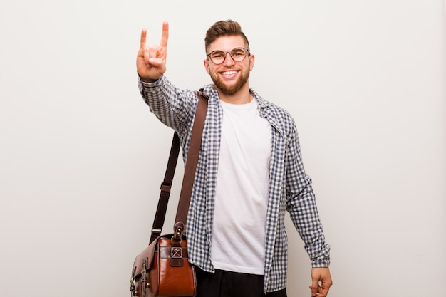 Young modern business man showing a horns gesture as a revolution concept.