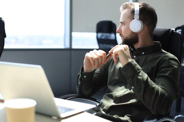 Молодой современный деловой человек, сидя в офисе.