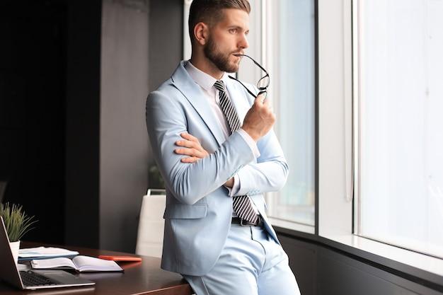 Молодой современный деловой человек думает о новом проекте, сидя в офисе.