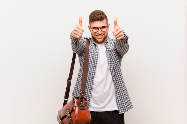 Young modern business man with thumbs ups, cheers about something