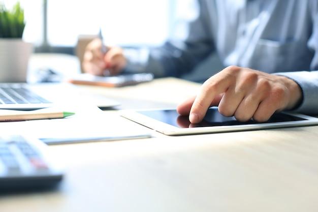 사무실에 앉아 있는 동안 디지털 태블릿을 사용하여 일하는 젊은 현대 사업가.