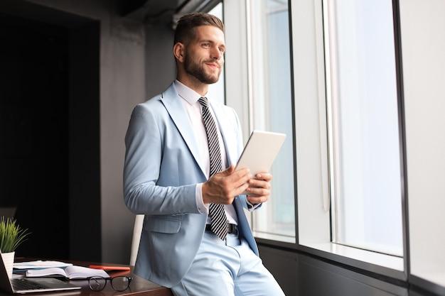 Молодой современный деловой человек, работающий с помощью цифрового планшета, сидя в офисе.