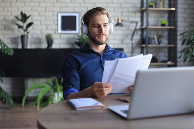 Молодой современный деловой человек, работающий с помощью ноутбука, сидя в домашнем офисе.