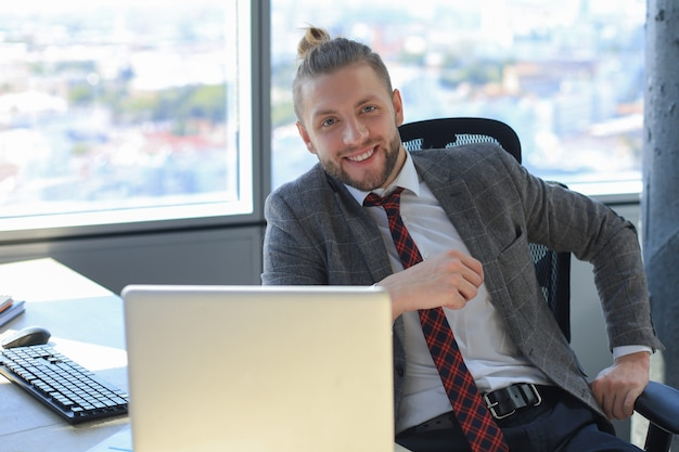 Молодой современный деловой человек, работающий с помощью ноутбука, сидя в офисе.