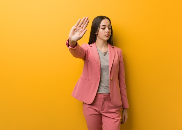 Young modern business woman putting hand in front