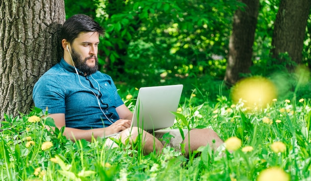 Young modern businessman freelancer working on computer and sitting on grass