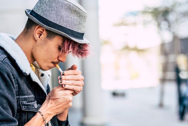 紫の髪と帽子の若い現代の白人のティーンエイジャーの男性はタバコに火をつける-喫煙と喫煙の人々の概念