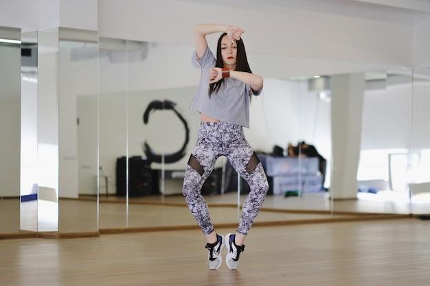 Молодая современная танцовщица танцует в студии