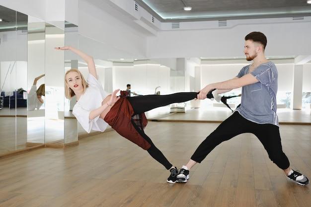Молодые современные танцоры танцуют в студии
