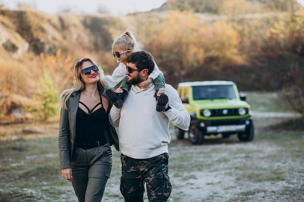 Молодая современная семья путешествует на машине и остановилась на прогулке в парке