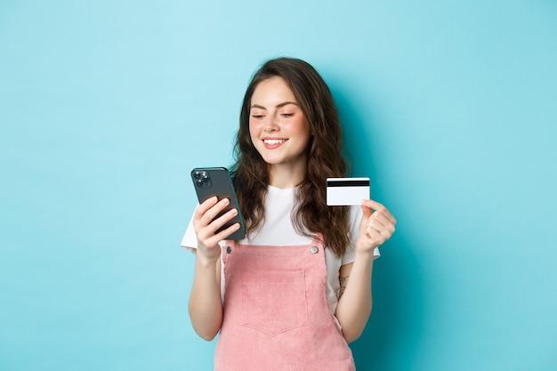 Молодая современная девушка платит онлайн с помощью кредитной карты, введите информацию на смартфоне, глядя на экран с довольным лицом, делая покупки в приложении, стоя на синем фоне.