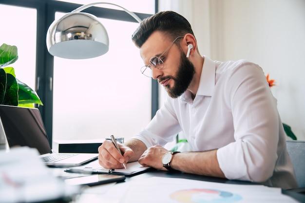Молодой современный красивый стильный бородатый бизнесмен в очках и белой рубашке работает на ноутбуке с документами, бумагами на столе офисного рабочего места.