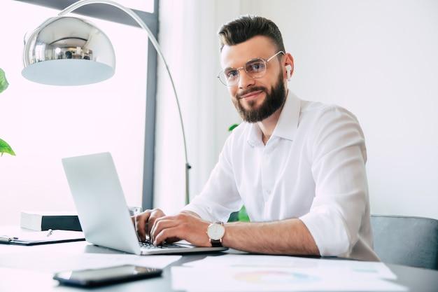 Молодой современный красивый стильный бородатый бизнесмен в очках и белой рубашке работает на ноутбуке с документами, бумагами на столе
