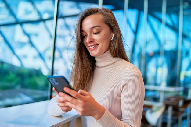 Young modern happy joyful woman wearing wireless headphones using smartphone for watching video online while sitting at cafe