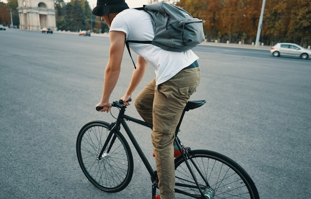 Young modern man cycling on a classic bike on the city road with a backpack