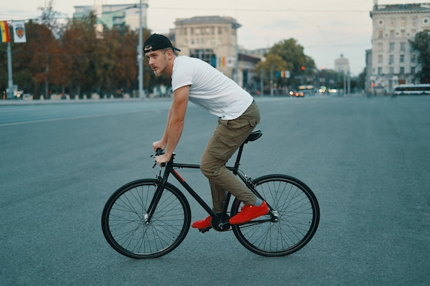 Young modern man cycling on a classic bike on the city road