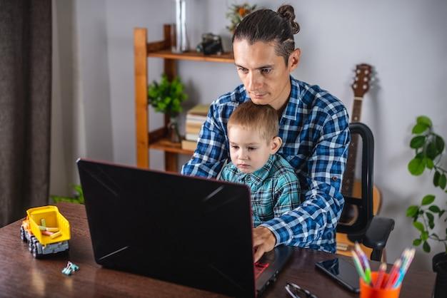 若い現代人の父親はラップトップに取り組んでおり、彼の幼い息子は彼の膝の上に座っています