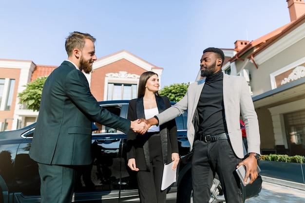 車の近くに立って、スマートカジュアルな服装の若い現代多民族男性が握手し、ビジネスセンターで屋外で会っている間笑顔します。近くに立って幸せな白人女性