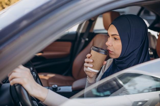 車の中でコーヒーを飲む若い現代のイスラム教徒の女性