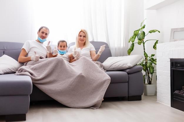 医療用マスクの若い現代の隔離されたコロナウイルス家族。家にいてパンデミックを止めなさい。一緒に自己隔離が解決策です。ケアコビッド-19。ママパパ娘ミレニアル世代