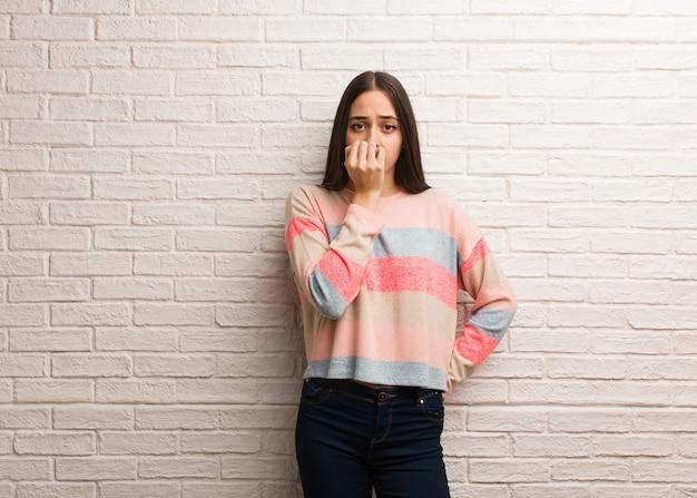 Молодая современная женщина кусает ногти, нервная и очень взволнованная