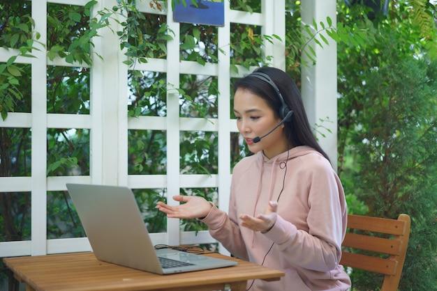 Молодая современная женщина, имея видеоконференции у себя дома